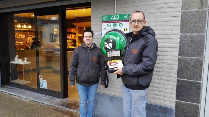 Bakker hangt en bekostigt zelf AED toestel - bakker en echtgenote met AED